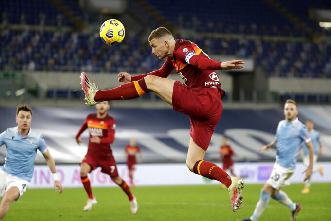Roma's Edin Dzeko aims for the ball during the Serie A soccer match between Lazio and Roma, at Rome's Olympic Stadium, Friday, Jan. 15, 2021. (AP Photo/Andrew Medichini)
