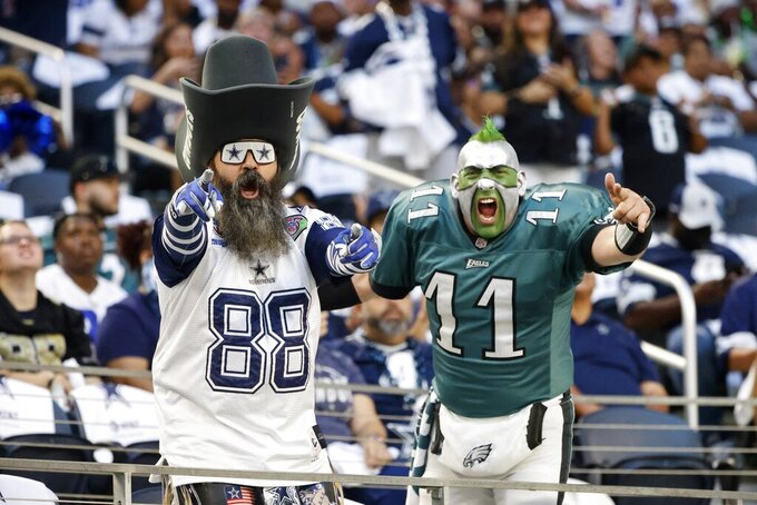 A Dallas Cowboys fan and a Philadelphia Eagles fan cheer at the start of the first half of an NFL football game in Arlington, Texas, Monday, Sept. 27, 2021. (AP Photo/Michael Ainsworth)