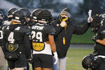 Brant McAdams, center, football coach at Pacific Lutheran, wears a mask as he talks to players during practice Tuesday, Feb. 2, 2021, in Tacoma, Wash. For all the attention heaped on the FBS level of college football last fall as it tried to play, it will not be the only college football during the 2020-21 sports calendar as a handful of NCAA Division III and NAIA programs begin some form of a winter/spring season Saturday, Feb. 6. (AP Photo/Ted S. Warren)
