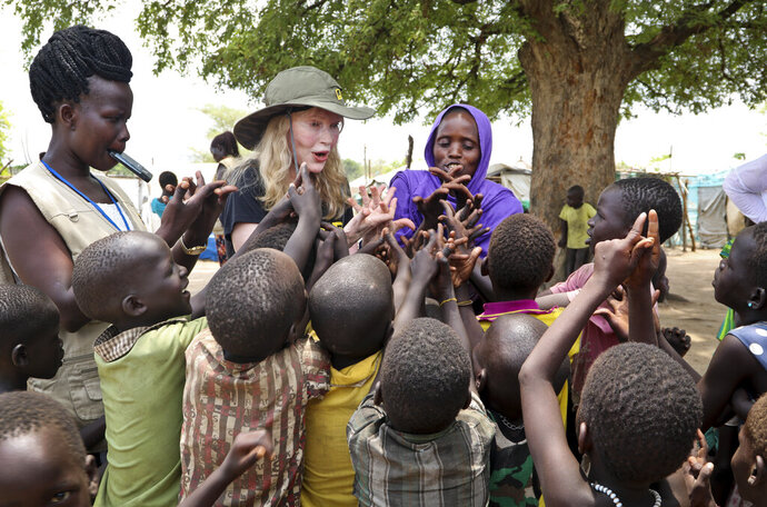 In this photo taken Tuesday, April 2, 2019, human rights activist Mia Farrow, center-left, plays a game with children during a visit to an internally displaced person's camp in the capital Juba, South Sudan. Human rights activist Mia Farrow spoke to The Associated Press as she visited South Sudan again in her new role as envoy for the International Rescue Committee, helping the aid group to promote a global initiative to change the way humanitarian organizations approach malnutrition. (AP Photo/Sam Mednick)