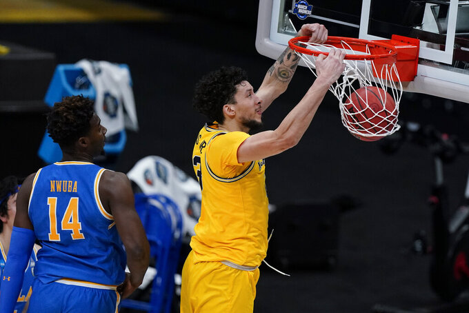Michigan forward Brandon Johns Jr. dunks the ball ahead of UCLA forward Kenneth Nwuba (14) during the first half of an Elite 8 game in the NCAA men's college basketball tournament at Lucas Oil Stadium, Tuesday, March 30, 2021, in Indianapolis. (AP Photo/Michael Conroy)