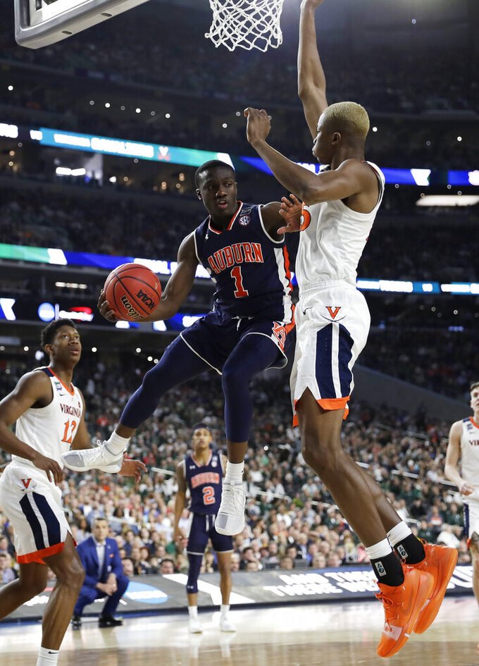 Auburn guard Jared Harper (1) drives to the basket past Virginia forward Mamadi Diakite, right, during the second half in the semifinals of the Final Four NCAA college basketball tournament, Saturday, April 6, 2019, in Minneapolis. (AP Photo/David J. Phillip)