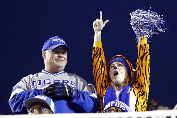 A Memphis fan, right, cheers in the second half of an NCAA college football game against Cincinnati, Friday, Nov. 29, 2019, in Memphis, Tenn. (AP Photo/Mark Humphrey)