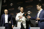 San Francisco Giants manager Gabe Kapler is given a new cap from general manager Scott Harris, right, as president of baseball operations Farhan Zaidi, left, looks on during a news conference at Oracle Park Wednesday, Nov. 13, 2019, in San Francisco. Kapler has been hired as manager of the San Francisco Giants, a month after being fired from the same job by the Philadelphia Phillies. Kapler replaces Bruce Bochy, who retired at the end of the season following 13 years and three championships with San Francisco. (AP Photo/Eric Risberg)