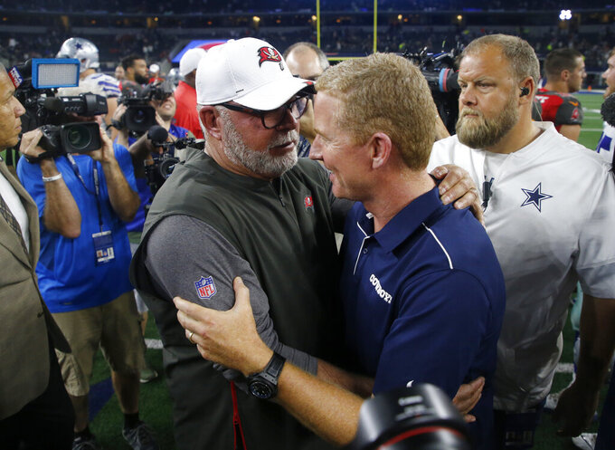 Tampa Bay Buccaneers head coach Bruce Arians, left, and Dallas Cowboys head coach Jason Garrett, right, greet each other after their preseason NFL football game in Arlington, Texas, Thursday, Aug. 29, 2019. (AP Photo/Michael Ainsworth)
