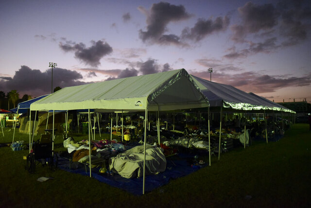 Tents and cots are set up for people whose homes are either destroyed or unsafe to enter after an 6.4 magnitude earthquake, at a baseball stadium amid aftershocks and no electricity in Guayanilla, Puerto Rico, at sunrise Friday, Jan. 10, 2020. Hundreds of thousands of Puerto Ricans are still without power and water, and thousands are staying in shelters and sleeping on sidewalks since Tuesday's earthquake. (AP Photo/Carlos Giusti)