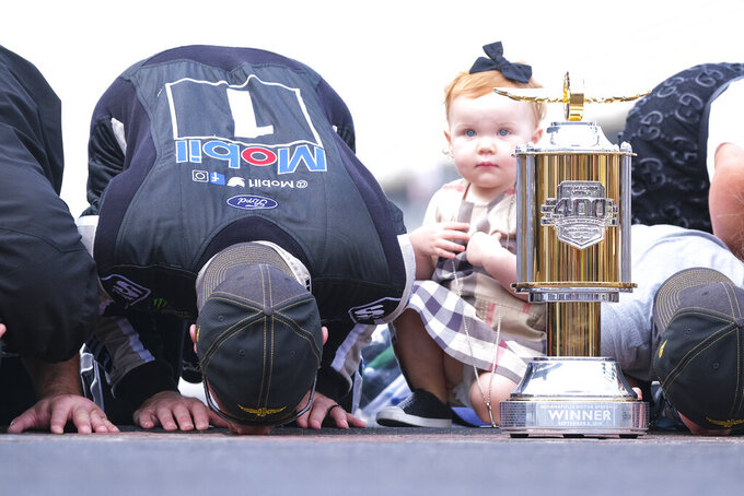 Piper Harvick looks on as her father Kevin Harvick kisses the yard of bricks on the finish line after winning the NASCAR Brickyard 400 auto race at Indianapolis Motor Speedway, Sunday, Sept. 8, 2019, in Indianapolis. (AP Photo/AJ Mast)