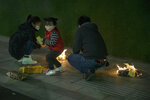 A family burn paper offerings for their departed relatives on the streets of Wuhan in central China's Hubei province on Saturday, April 4, 2020. Authorities are controlling access and limiting the number of people entering cemeteries across China during the annual Qingming festival, also known as the Grave Sweeping Day, a day when Chinese around the world remember their dearly departed and take time off to clean up the tombs and place flowers and offerings, a move to prevent the spread of the new coronavirus outbreak. (AP Photo/Ng Han Guan)