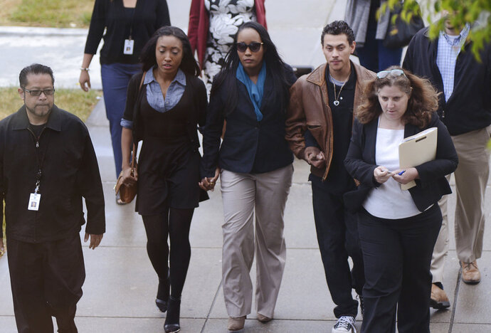 In this photo provided by the Daily Republic, Ina Rogers, center, walks to Solano County Superior Court in Fairfield, Calif., Wednesday, May 16, 2018, to face multiple charges of felony child abuse. Bail for a California mother of 10 children who officials say suffered long-term abuse was set at nearly $500,000 after the judge said she remains a danger to the kids. Prosecutors charged Rogers, 31, on Wednesday in Solano Superior Court with nine counts of felony child abuse, saying that she caused the children to be in a situation likely to produce great bodily injury and death. Her husband, Jonathan Allen, faces multiple charges of torture and felony child abuse. He has pleaded not guilty and remains in Solano County Jail on $5.2 million bail. (Robinson Kuntz/Daily Republic via AP)