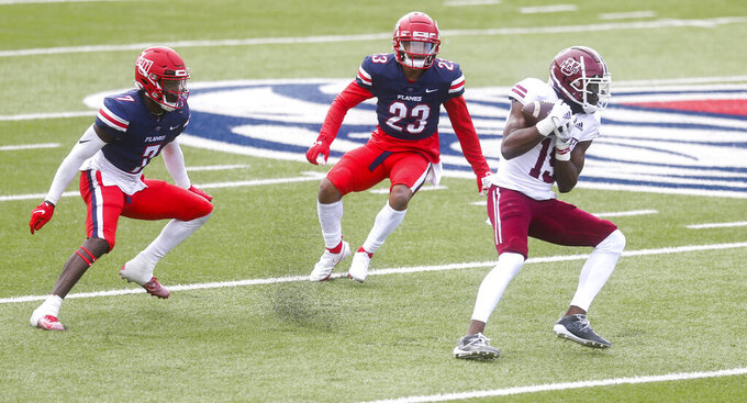 Massachusetts wide receiver Samuel Emilus (19) makes a catch as he is defended by Liberty safeties Cedric Stone (23) and Marcus Haskins (7) during the first half of a NCAA college football game on Friday, Nov. 27, 2020, at Williams Stadium in Lynchburg, Va. (AP Photo/Shaban Athuman)