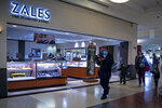 Shoppers walk past a Zales jewelry store inside the Kings Plaza Mall, Tuesday Oct. 20, 2020, in New York. The coronavirus pandemic is transforming holiday hiring this year, with companies starting hiring earlier and offering extra safety protocols. Zales plans to hire 4,000 holiday workers. (AP Photo/Bebeto Matthews)