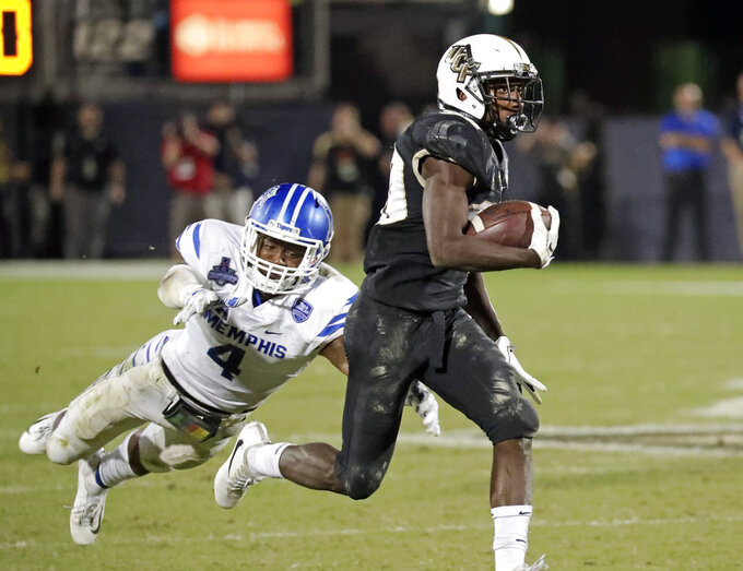 Central Florida running back Greg McCrae, right, runs for yardage on a fourth and one play past Memphis defensive back Josh Perry (4) during the second half of the American Athletic Conference championship NCAA college football game, Saturday, Dec. 1, 2018, in Orlando, Fla. (AP Photo/John Raoux)