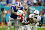 Miami Dolphins quarterback Jacoby Brissett (14) is sacked by Buffalo Bills defensive end A.J. Epenesa (57) during the second half of an NFL football game, Sunday, Sept. 19, 2021, in Miami Gardens, Fla. (AP Photo/Wilfredo Lee)
