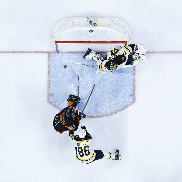 Philadelphia Flyers' Sean Couturier (14) scores a goal past Boston Bruins' Jaroslav Halak (41) and Kevan Miller (86) during the second period of an NHL hockey game, Wednesday, Jan. 16, 2019, in Philadelphia. (AP Photo/Matt Slocum)