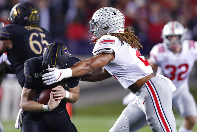 Ohio State defensive end Chase Young, right, sacks Northwestern quarterback Aidan Smith during the first half of an NCAA college football game Friday, Oct. 18, 2019, in Evanston, Ill. (AP Photo/Charles Rex Arbogast)