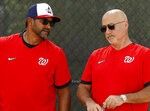FILE - In this Feb. 17, 2020, file photo, Washington Nationals manager Dave Martinez, left, talks with general manager Mike Rizzo during spring training baseball practice in West Palm Beach, Fla. Armed with a new multiyear contract, Rizzo says his top priority is working on a new deal for Martinez. The team has a club option for Martinez for 2021, but Rizzo says he prefers a long-term deal for the manager. (AP Photo/Jeff Roberson, File)