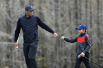 """FILE - Tiger Woods, left, gives his son Charlie a fist bump after Charlie made a putt on the 12th green during a practice round of the Father Son Challenge golf tournament,\ in Orlando, Fla., in this Thursday, Dec. 17, 2020, file photo. Woods was injured Tuesday, Feb. 23, 2021, in a vehicle rollover in Los Angeles County and had to be extricated from the vehicle with the """"jaws of life"""" tools, the Los Angeles County Sheriff's Department said. (AP Photo/Phelan M. Ebenhack, File)"""