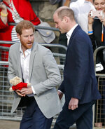 "FILE - In this file photo dated Friday, May 18, 2018, Britain's Prince William, right, and Prince Harry return to Windsor Castle after greeting crowds in Windsor, England.  Prince Harry will attend the funeral for Prince Philip on Saturday April 17, and many observers believe that the funeral will provide an ideal opportunity for ""The Firm"" to show a united front to the world and for the brothers to smooth over tensions.(AP Photo/Frank Augstein, FILE)"