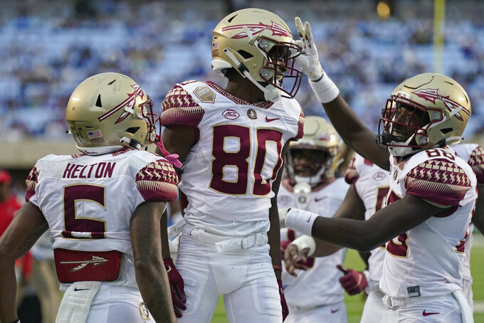 Florida State wide receiver Ontaria Wilson (80) is congratulated by wide receivers Keyshawn Helton (6) and Kentron Poitier (88) following Wilson's touchdown against North Carolina during the second half of an NCAA college football game in Chapel Hill, N.C., Saturday, Oct. 9, 2021. (AP Photo/Gerry Broome)