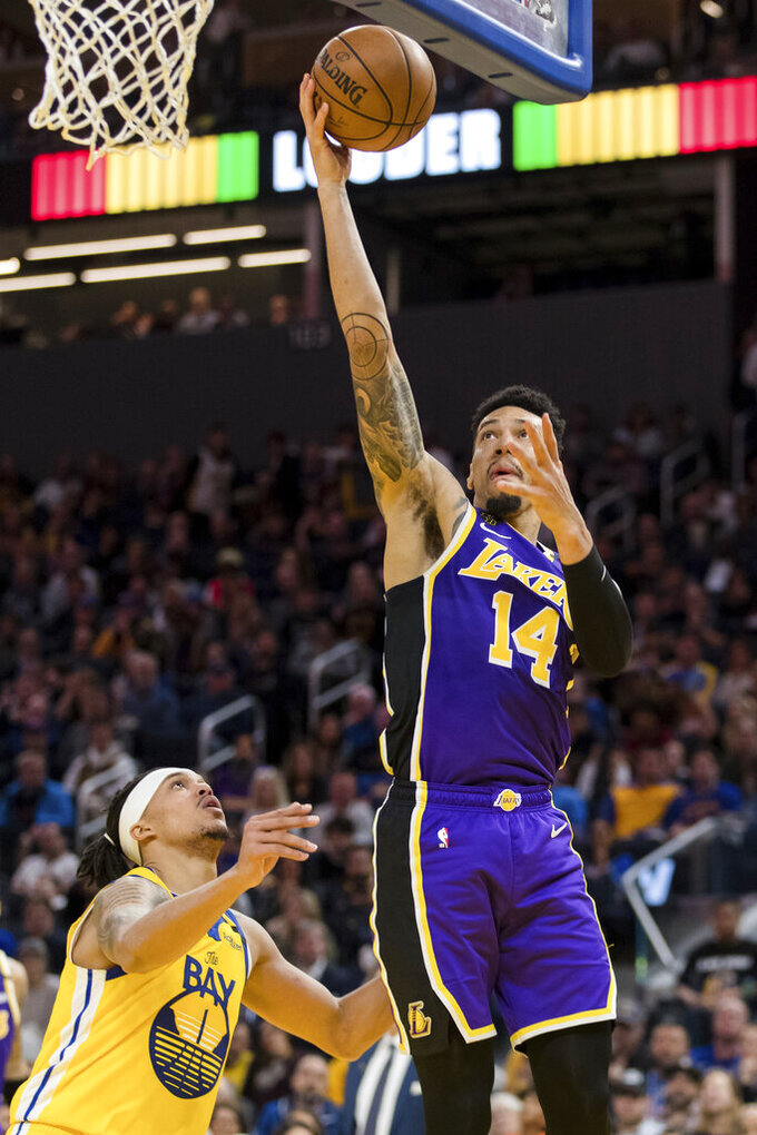 FILE - Los Angeles Lakers guard Danny Green (14) shoots as Golden State Warriors guard Damion Lee (1) defends in the first half of an NBA basketball game in San Francisco, in this Saturday, Feb. 8, 2020, file photo. Teams may begin making trades Monday, according to a memo sent to teams and obtained early Sunday, Nov. 15, 2020, by The Associated Press. And the first deal known to be tentatively agreed upon would send guard Dennis Schröder from Oklahoma City to the champion Los Angeles Lakers for Danny Green and the No. 28 pick in Wednesday's draft, a person with knowledge of that agreement told the AP. (AP Photo/John Hefti, File)