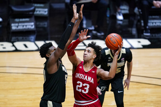 Indiana forward Trayce Jackson-Davis (23) shoots over Purdue forward Trevion Williams (50) during the first half of an NCAA college basketball game in West Lafayette, Ind., Saturday, March 6, 2021. (AP Photo/Michael Conroy)