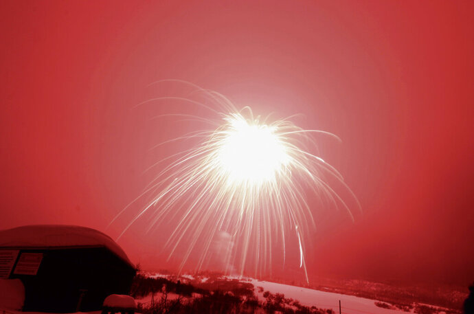 In this Saturday, Feb. 8, 2020 photo, a firework launched over Colorado ski resort town Steamboat Springs Saturday, Feb. 8, 2020. The firework has set a record as the world's largest aerial firework. The 2,800-pound shell flew 2,200 feet above the Steamboat Springs Winter Carnival before it burst on Saturday night.  Guinness World Records representatives witnessed and certified the record.   (Derek Maiolo /Steamboat Pilot & Today via AP)
