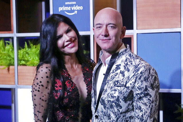FILE - In this Jan. 16, 2020, file photo, Amazon CEO Jeff Bezos, right and his girlfriend Lauren Sanchez poses for photographs during a blue carpet event organized by Amazon Prime Video in Mumbai, India. Michael Sanchez, the brother of Jeff Bezos's girlfriend, is suing the Amazon founder for defamation, alleging that Bezos and his team falsely told reporters that he provided nude photos of Bezos to the The National Enquirer.  (AP Photo/Rafiq Maqbool, File)