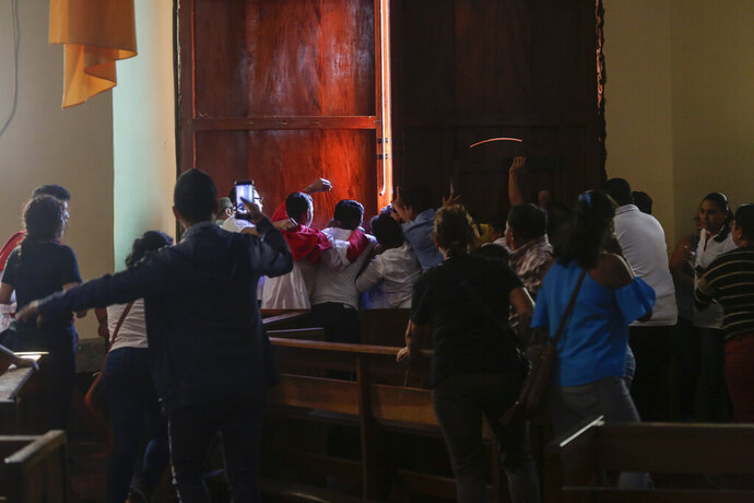 Parishioners and altar boys repel supporters of President Daniel Ortega who are trying to enter the San Juan Bautista Church by force, in Masaya, Nicaragua, Thursday, Nov. 21, 2019. The pro-Ortega group disrupted a mass in support of a group of mothers who are engaged in a hunger strike at the San Miguel Church in Masaya, to demand the release of their sons and daughters who are imprisoned by the Ortega government. (AP Photo/Alfredo Zuniga)