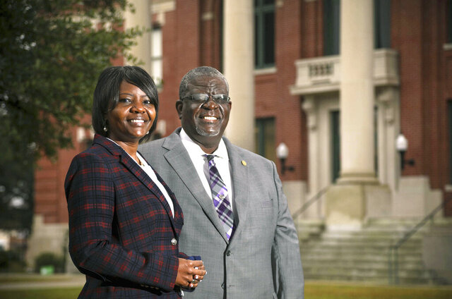 Kevin L. Johnson, a South Carolina Senator, poses with his daughter, Kimberly O. Johnson, a newly elected member of the S.C. House of Representatives,  in front of the Manning Courthouse where they live in Manning, S.C., on Thursday, Dec. 17, 2020. (Tracy Glantz/The State via AP)