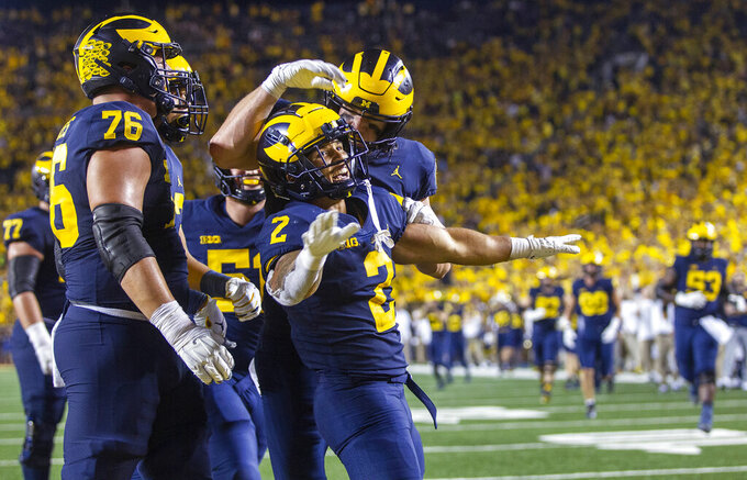 Michigan running back Blake Corum (2) celebrates a touchdown with teammates during the fourth quarter of an NCAA college football game against Washington in Ann Arbor, Mich., Saturday, Sept. 11, 2021. (AP Photo/Tony Ding)