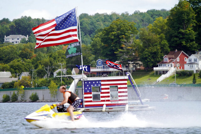A jet skier passes a patriotic shanty-boat owned by AJ Crea on Pontoosuc Lake on Labor Day in Pittsfield, Mass., Monday, Sept. 7, 2020. (Ben Garver/The Berkshire Eagle via AP)
