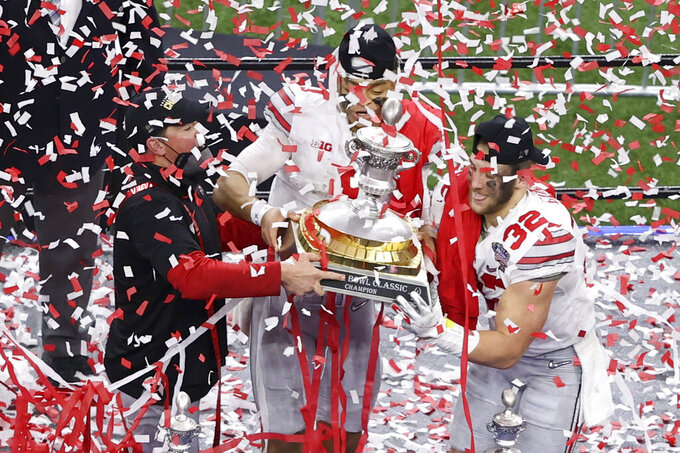Ohio State head coach Ryan Day, from left, quarterback Justin Fields and linebacker Tuf Borland hold up the trophy after their win against Clemson in the Sugar Bowl NCAA college football game Friday, Jan. 1, 2021, in New Orleans. Ohio State won 49-28. (AP Photo/Butch Dill)