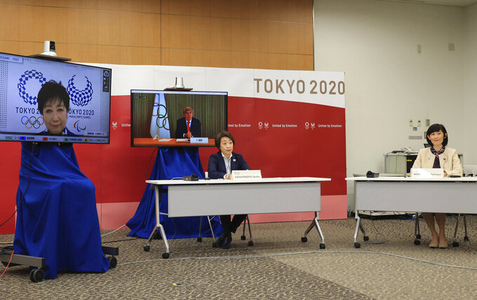 International Olympic Committee (IOC) President Thomas Bach, on right screen, delivers an opening speech while Tokyo 2020 Organizing Committee president Seiko Hashimoto, front left, Tokyo Gov. Yuriko Koike, on left screen, and Japanese Olympic Minister Tamayo Marukawa listen at a five-party meeting of Tokyo 2020 Olympic and Paralympic Games with International Paralympic Committee (IPC) President Andrew Parsons in Tokyo Saturday, March 20, 2021.  (Yoshikazu Tsuno/Pool Photo via AP)