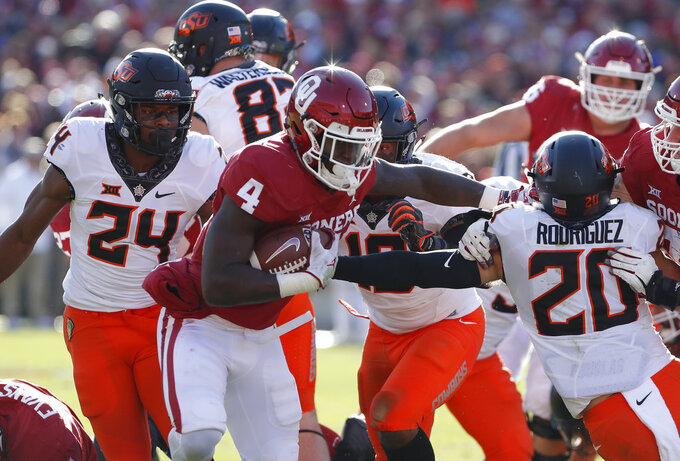 Oklahoma running back Trey Sermon (4) escapes a tackle by Oklahoma State safety Jarrick Bernard (24) and safety Malcolm Rodriguez (20) in the first half of an NCAA college football game in Norman, Okla., Saturday, Nov. 10, 2018. (AP Photo/Alonzo Adams)