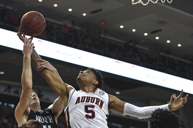 North Florida's Garrett Sams (11) stops a rebound by Auburn forward Chuma Okeke (5) during the first half of an NCAA college basketball game Saturday, Dec. 29, 2018, in Auburn, Ala. (AP Photo/Julie Bennett)