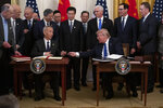 In this Jan. 15, 2020, photo, President Donald Trump hands a pen to Chinese Vice Premier Liu He after signing