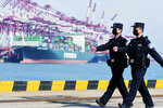 In this Feb. 19, 2020, photo, police officers wearing face masks patrol at a container port in Qingdao in eastern China's Shandong Province. China on Friday, Feb. 21 suspended more punitive tariffs on imports of U.S. industrial goods in response to a truce in its trade war with Washington that threatened global economic growth. (Chinatopix via AP)