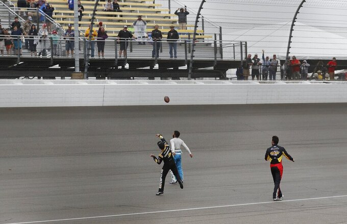 Daniel Hemric, left, Bubba Wallace, center, and Corey LaJoie wait out a rain delay as they toss a football with fans at the NASCAR cup series auto race at Michigan International Speedway, Sunday, June 9, 2019, in Brooklyn, Mich. The race has been rescheduled for Monday. (AP Photo/Carlos Osorio)