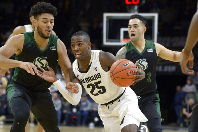 Colorado guard McKinley Wright IV (25) drives between Sacramento State's guards Ethan Esposito, left, and Izayah Mauriohooho-Le'Afa, back right, in the first half of an NCAA college basketball game, Saturday, Nov. 30, 2019, in Boulder, Colo. (AP Photo/Cliff Grassmick)