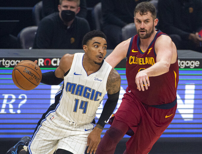 Orlando Magic's Gary Harris (14) drives past Cleveland Cavaliers' Kevin Love during the first quarter of an NBA basketball game Wednesday, April 28, 2021 in Cleveland. (AP Photo/Phil Long)