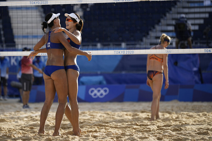 Xue Chen, left, of China, and teammate Wang Zinzin celebrate winning a women's beach volleyball match against the Netherlands at the 2020 Summer Olympics, Tuesday, July 27, 2021, in Tokyo, Japan. (AP Photo/Felipe Dana)
