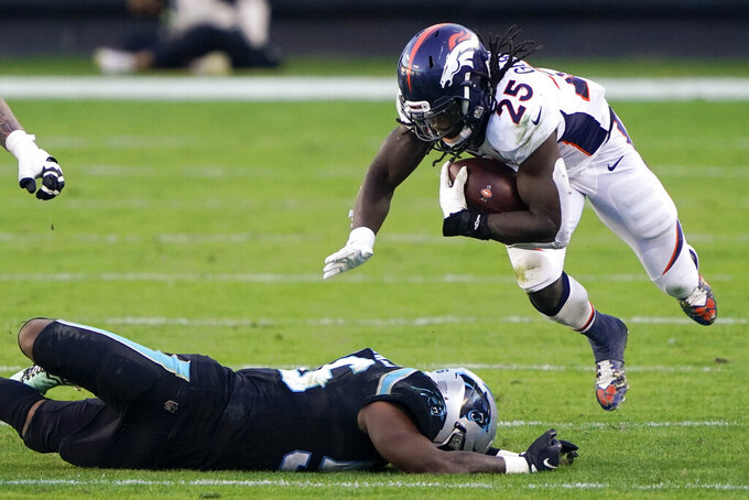 Denver Broncos running back Melvin Gordon III is tackled by Carolina Panthers linebacker Jermaine Carter during the second half of an NFL football game Sunday, Dec. 13, 2020, in Charlotte, N.C. (AP Photo/Brian Blanco)