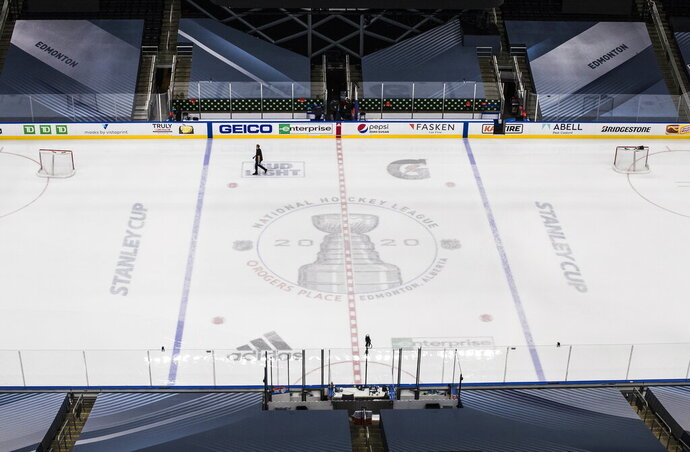 Ice crews work at the NHL playoffs venue in Edmonton, Alberta, Friday, Aug. 28, 2020. Boston Bruins captain Zdeno Chara hopes players and fans take a step back to pause and reflect on racial justice issues as the NHL takes a second day off from second-round series action on Friday, before games resume on Saturday. (Jason Franson/The Canadian Press via AP)