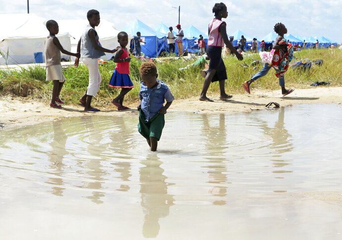 A child plays in a puddle at a camp for displaced survivors of cyclone Idai in Beira, Mozambique,Tuesday, April, 2, 2019. Mozambican and international health workers raced Monday to contain a cholera outbreak in the cyclone-hit city of Beira and surrounding areas, where the number of cases has jumped to more than 1,000. (AP Photo/Tsvangirayi Mukwazhi)
