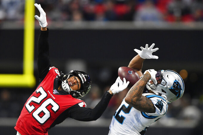 Carolina Panthers wide receiver D.J. Moore (12) makes ther catch against Atlanta Falcons cornerback Isaiah Oliver (26) during the first half of an NFL football game, Sunday, Dec. 8, 2019, in Atlanta. (AP Photo/John Amis)