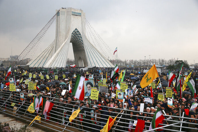 Iranians attend a ceremony celebrating the 40th anniversary of the Islamic Revolution, at the Azadi, or Freedom Tower, in Tehran, Iran, Monday, Feb. 11, 2019. Hundreds of thousands of people poured out onto the streets of Tehran and other cities and towns across Iran, marking the date 40 years ago that is considered victory day in the country's 1979 Islamic Revolution. (AP Photo/Vahid Salemi)