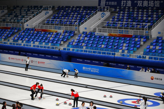 "Local teams compete in a curling competition during a test event for the 2022 Beijing Winter Olympics at the National Aquatic Center, also known as the ""Water Cube"" in Beijing, Saturday, April 3, 2021. The organizers of the 2022 Beijing Winter Olympics has started 10 days of testing for several sport events in five different indoor venues from April 1-10, becoming the first city to hold both the Winter and Summer Olympics. (AP Photo/Andy Wong)"