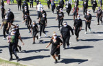 """People dance to Jerusalema in Cape Town, South Africa, Thursday, Sept. 24, 2020. South Africans of all walks of life are dancing to """"Jerusalema,"""" a rousing anthem to lift their spirits amid the battle against COVID-19. In response to a call from President Cyril Ramaphosa to mark the country's Heritage Day holiday Thursday, people from townships to posh suburbs are doing line dances to the tune. (AP Photo/Nardus Engelbrecht)"""