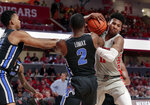 Houston guard Nate Hinton, right, battles to keep the ball from Memphis guard Antwann Jones, left, and Memphis guard Alex Lomax (2) during the second half of an NCAA college basketball game Sunday, Jan. 6, 2019, in Houston. (AP Photo/Michael Wyke)