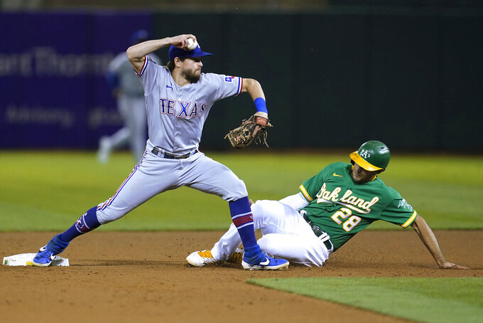 Texas Rangers second baseman Nick Solak, left, throws to first base after forcing Oakland Athletics' Matt Olson (28) out at second base during the fourth inning of a baseball game in Oakland, Calif., Friday, Sept. 10, 2021. Matt Chapman was safe at first. (AP Photo/Jeff Chiu)